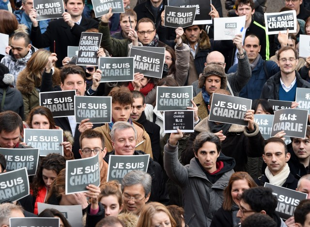 French residents hold signs reading