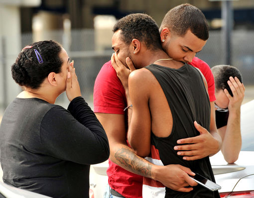 Friends and family members embrace outside the Orlando Police Headquarters after a shooting at the Pulse night club in Orlando
